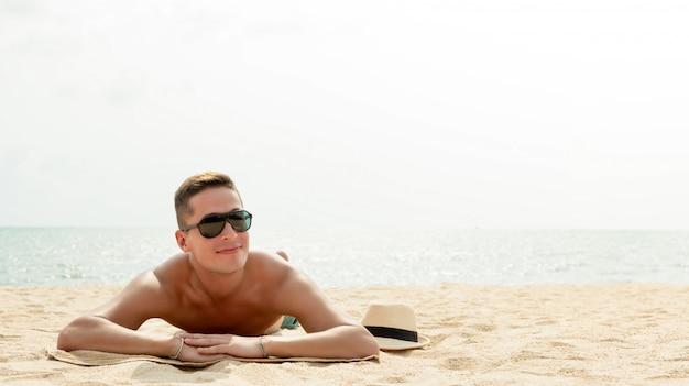 Hombre hermoso joven que miente en la playa en vacaciones de verano