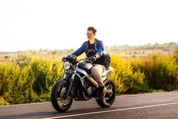 Hombre hermoso joven que monta en la moto en el camino del campo.