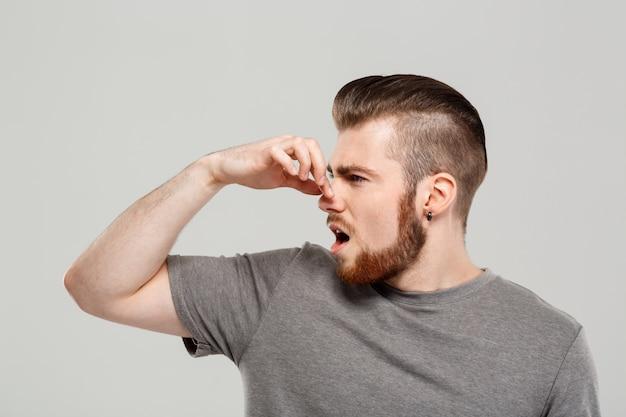 Hombre hermoso joven que pellizca la nariz sobre la pared gris.