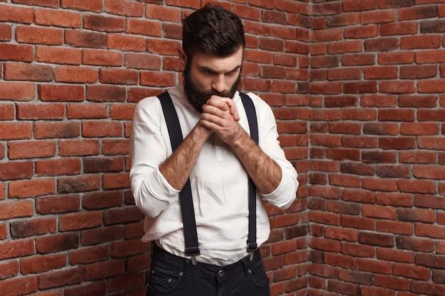 Hombre hermoso joven que piensa posando en la pared de ladrillo.