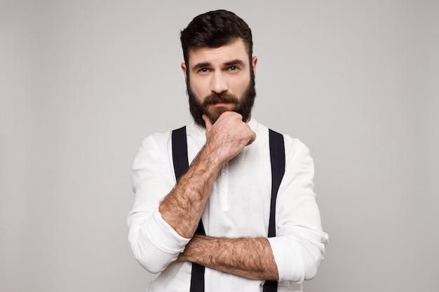 Hombre hermoso joven que piensa posando sobre blanco.