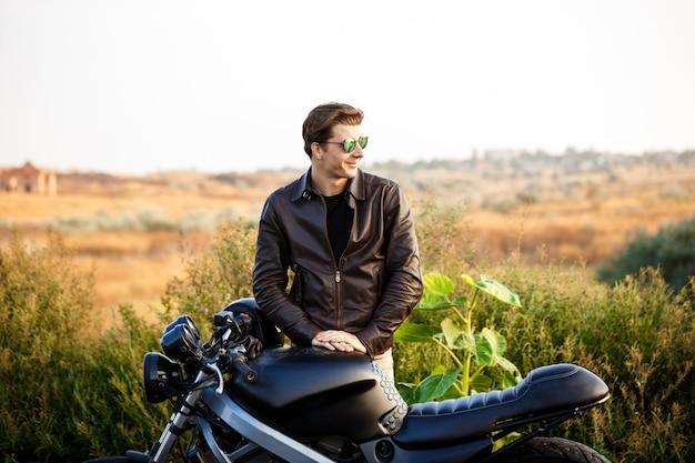 Hombre hermoso joven que presenta cerca de su moto en el camino del campo.