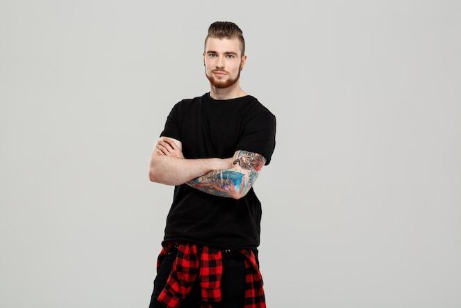 Hombre hermoso joven que presenta sobre la pared gris.