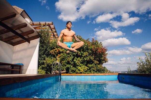 Hombre hermoso joven que salta a la piscina con felicidad en su cara. modelo masculino volando por encima del agua.