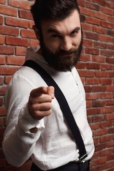 Hombre hermoso joven que señala el dedo en la pared de ladrillo.