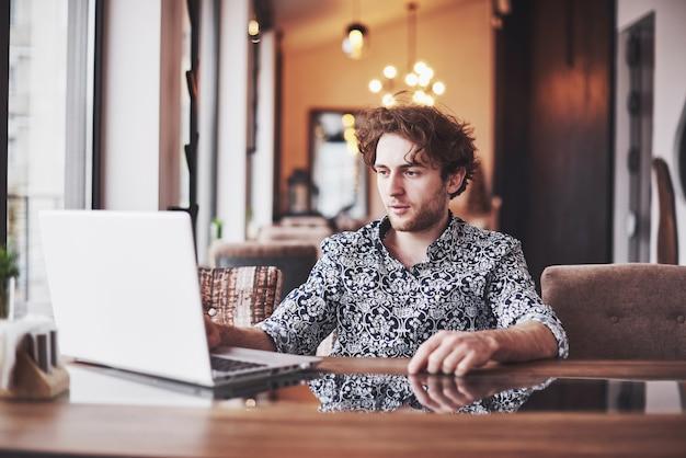Hombre hermoso joven que se sienta en café y que trabaja en la computadora portátil.