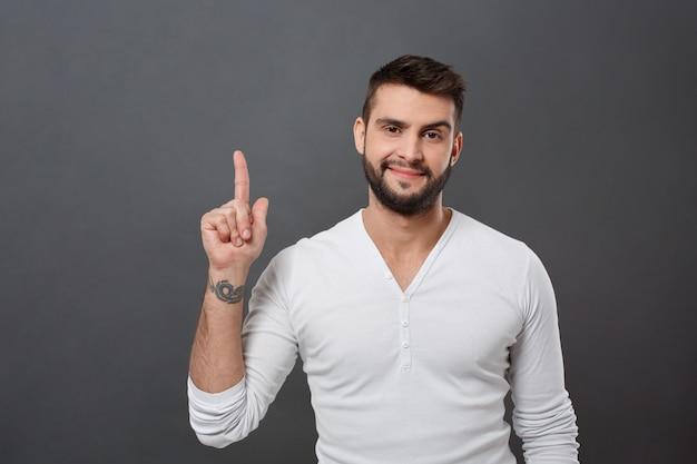 Hombre hermoso joven que sonríe apuntando el dedo hacia arriba sobre la pared gris