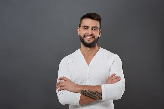 Hombre hermoso joven que sonríe con los brazos cruzados sobre la pared gris
