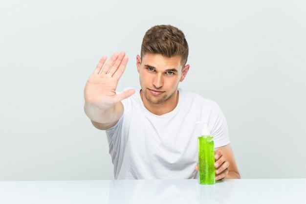 Hombre hermoso joven que sostiene una botella del áloe vera que se coloca con la mano extendida que muestra la señal de stop, previniéndole.