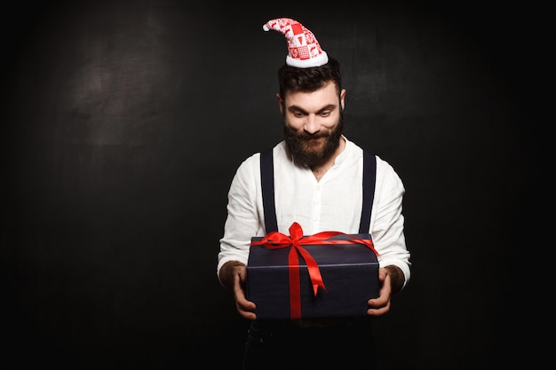 Hombre hermoso joven que sostiene la caja de regalo de la navidad sobre negro.
