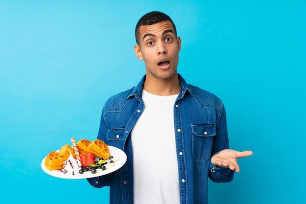 Hombre hermoso joven que sostiene las galletas sobre la pared azul aislada que hace gesto de las dudas mientras que levanta los hombros