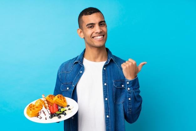 Hombre hermoso joven que sostiene las galletas sobre la pared azul aislada que señala al lado para presentar un producto