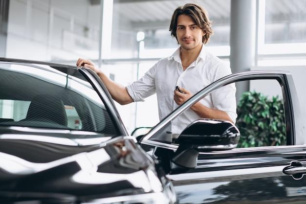 Hombre hermoso joven que sostiene llaves en una sala de exposición del coche
