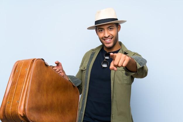 El hombre hermoso joven que sostiene un maletín de la vendimia sobre la pared azul aislada señala con el dedo a usted con una expresión confiada