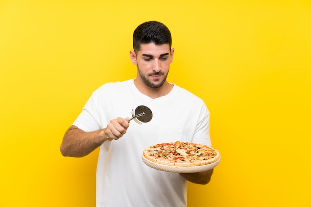 Hombre hermoso joven que sostiene una pizza sobre la pared amarilla aislada