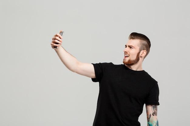 Hombre hermoso joven que sostiene el teléfono que hace el selfie sobre la pared gris.