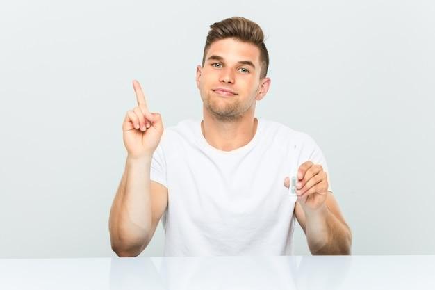 Hombre hermoso joven que sostiene un termómetro que muestra el número uno con el dedo.