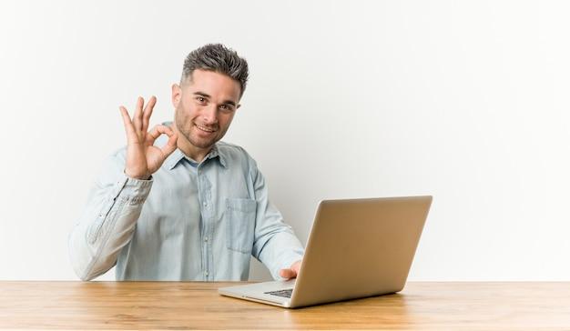 Hombre hermoso joven que trabaja con su computadora portátil alegre y confidente que muestra gesto aceptable.