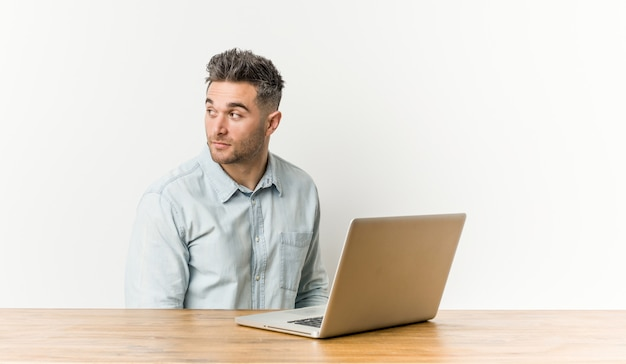El hombre hermoso joven que trabaja con su computadora portátil parece a un lado sonriente, alegre y agradable.