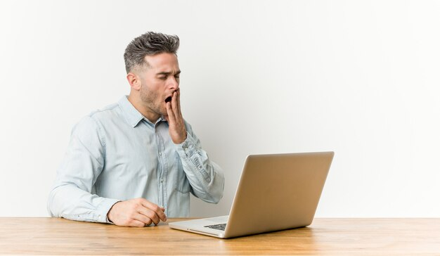 Hombre hermoso joven que trabaja con su computadora portátil que bosteza mostrando un gesto cansado que cubre la boca con la mano.