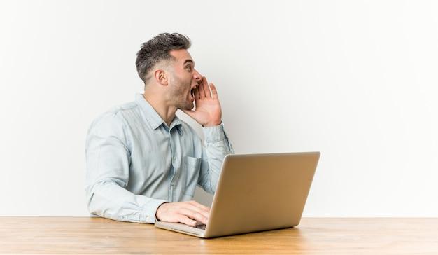 Hombre hermoso joven que trabaja con su computadora portátil que grita y que sostiene la palma cerca de boca abierta.