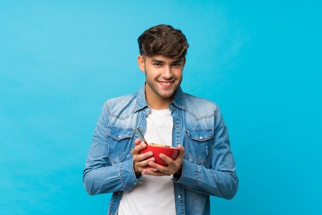 Hombre hermoso joven sobre azul aislado que sostiene un tazón de cereales