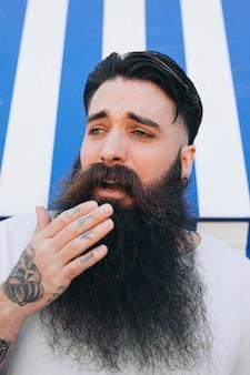 Hombre hermoso joven sorprendido que toca su barba con la mano
