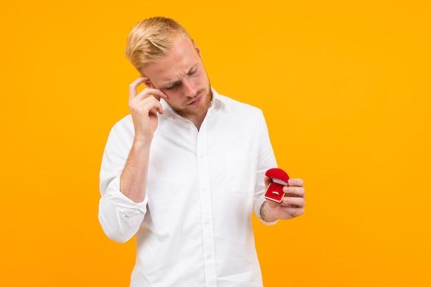 El hombre hermoso joven sostiene un anillo de compromiso para su novia y llama al teléfono aislado en amarillo