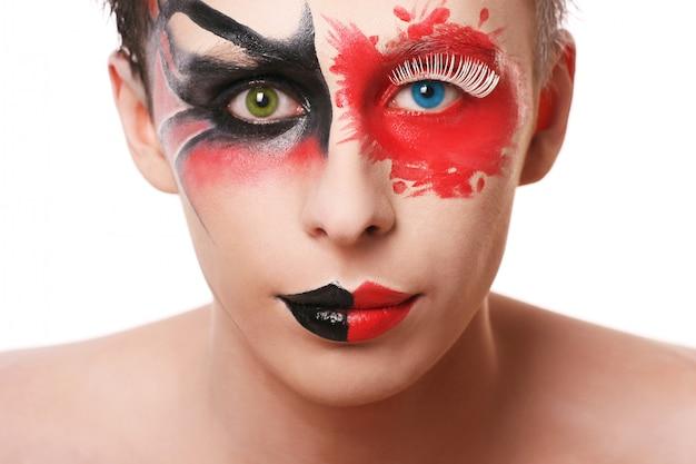 Hombre hermoso con maquillaje abstracto en blanco