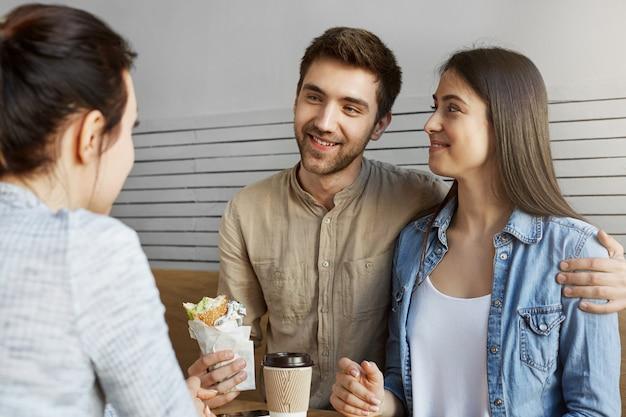 Hombre hermoso con el pelo oscuro en ropa elegante que presenta a su novia a la madre en café. beben café, comen, ríen y hablan sobre el futuro.