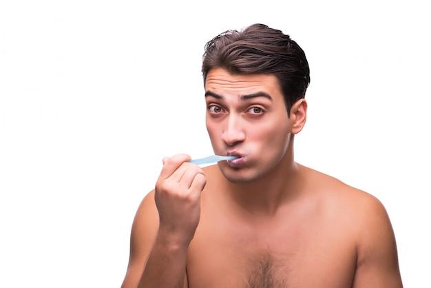 Hombre hermoso que cepilla sus dientes aislados en blanco