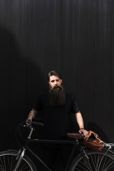 Hombre hermoso que se coloca con la bicicleta y el bolso de hombro contra el contexto negro oscuro