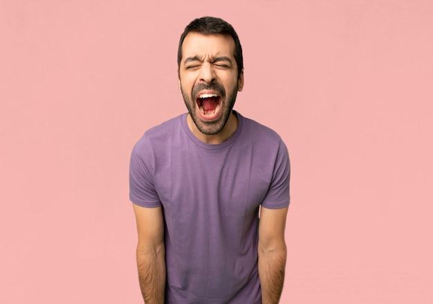 Hombre hermoso que grita al frente con la boca abierta sobre fondo rosado aislado