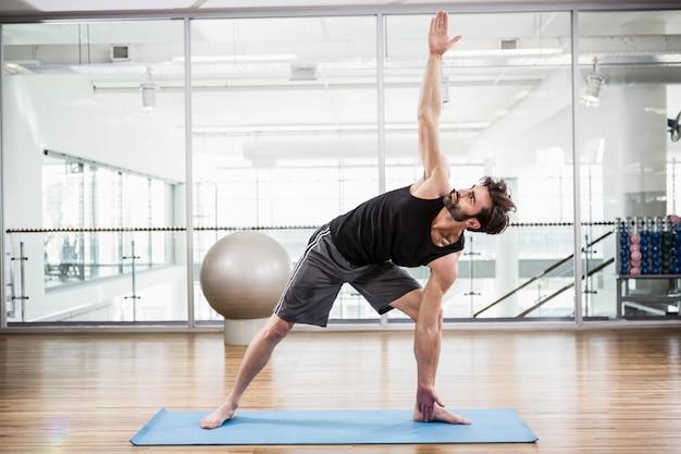 Hombre hermoso que hace yoga en la estera en el estudio