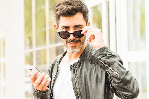 Hombre hermoso que mira a escondidas a través de las gafas de sol que sostienen el teléfono móvil