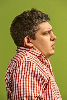 Hombre hermoso que parece sorprendido y desconcertado aislado en la pared verde