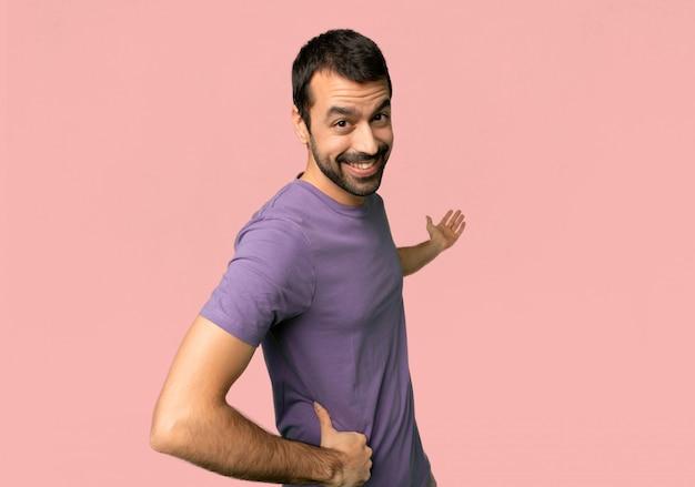 Hombre hermoso que señala detrás y que presenta un producto en fondo rosado aislado