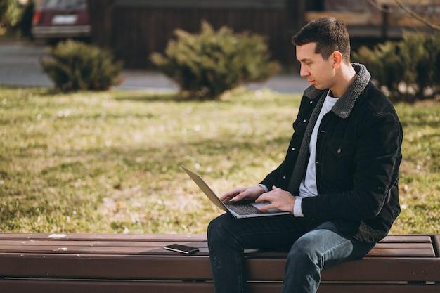 Hombre hermoso que se sienta en un banco usando la computadora portátil en parque