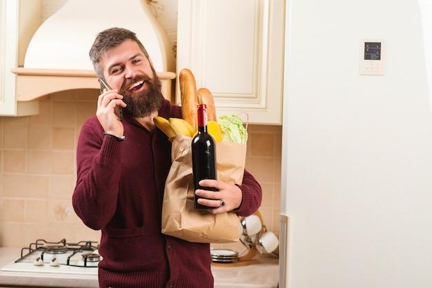 Hombre hermoso que sostiene la bolsa de papel llena de ultramarinos frescos en casa. hombre barbudo con una botella de vino.