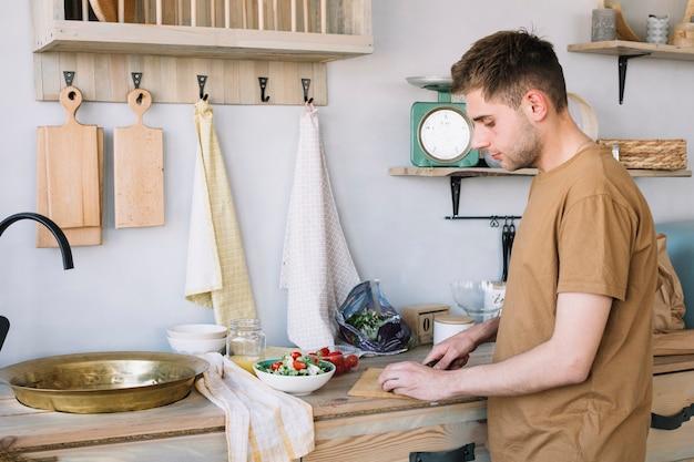 Hombre hermoso que taja verduras en la tabla de cortar para hacer la ensalada