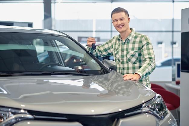 Hombre hermoso rubio que compra el vehículo gris en salón del coche.