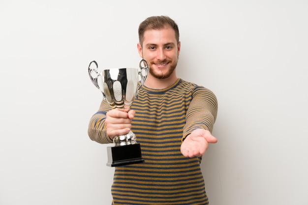 Hombre hermoso sobre la pared blanca aislada que sostiene un trofeo