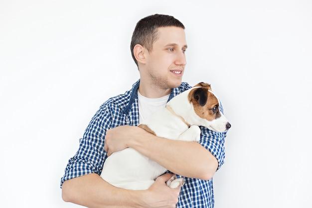 Un hombre hermoso sonriente que sostiene un perro criado en línea pura en un blanco. el concepto de personas y animales. joven sosteniendo a su perro en sus brazos con amor y jugando con él, contra un blanco
