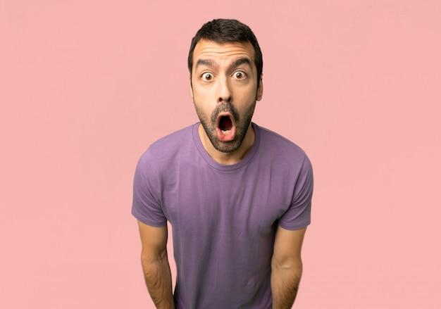 Hombre hermoso con sorpresa y expresión facial chocada en fondo rosado aislado