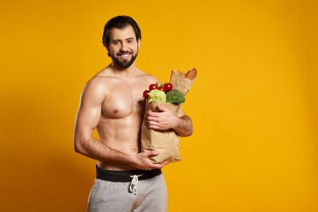El hombre hermoso sostiene la bolsa de papel con la comida fresca.