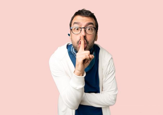 El hombre hermoso con los vidrios que muestran una muestra del gesto del silencio que pone el dedo en boca en fondo rosado aislado