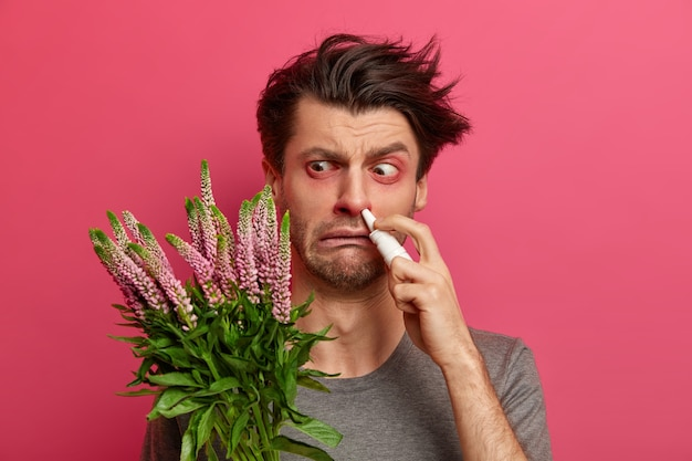 El hombre hipersensible tiene fiebre del heno, su sistema inmunológico reacciona a sustancias extrañas, tiene los ojos rojos hinchados, usa gotas nasales para un tratamiento efectivo, permanece en interiores. concepto de alergia y rinitis estacional