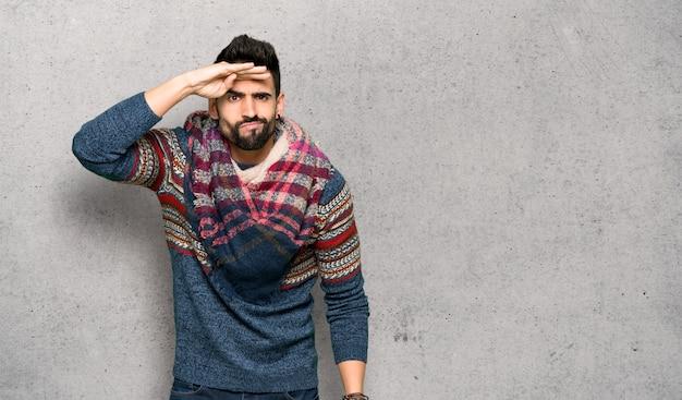 Hombre hippie que mira lejos con la mano para mirar algo sobre la pared con textura