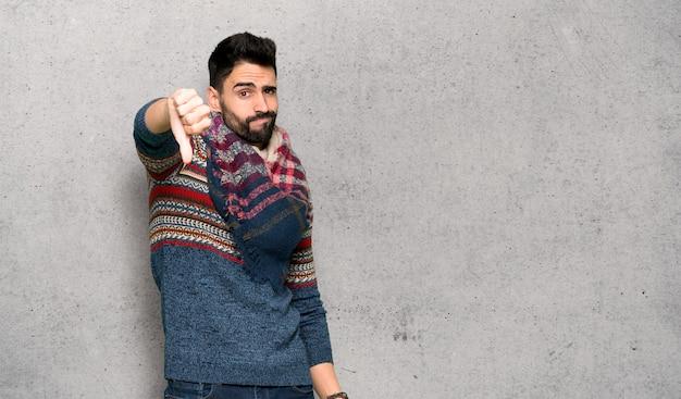 Hombre hippie que muestra el pulgar hacia abajo con expresión negativa sobre una pared texturizada