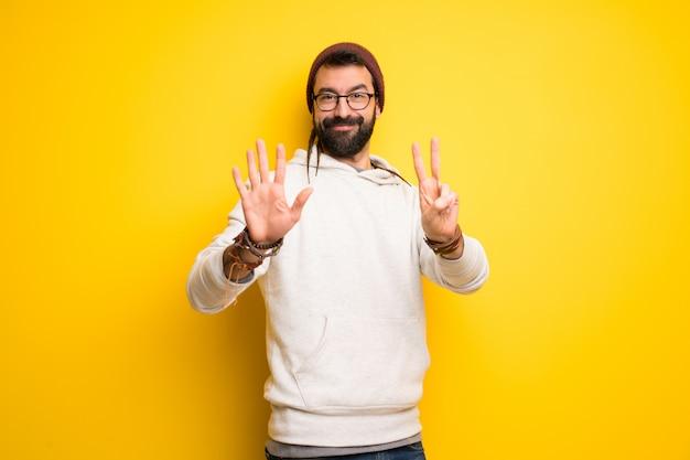 Hombre hippie con rastas contando siete con los dedos